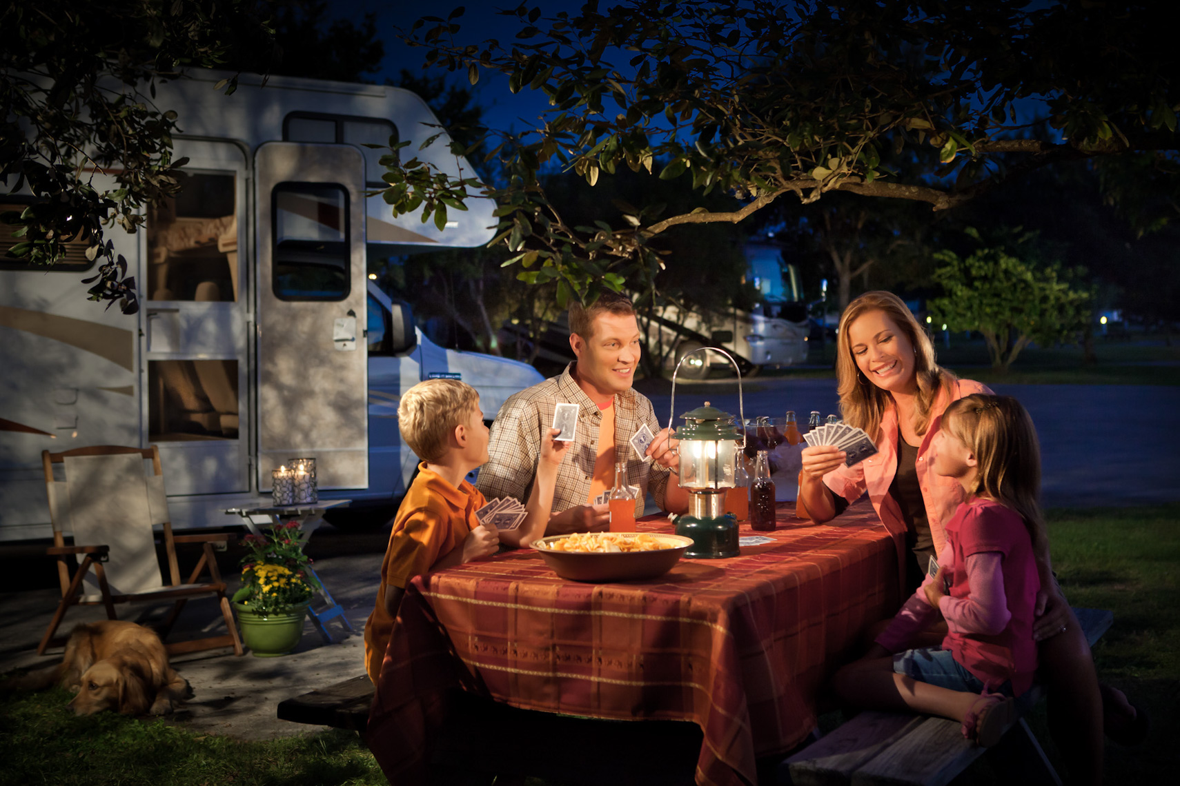Family camping and eating at picnic table, shot by Steven P. Widoff