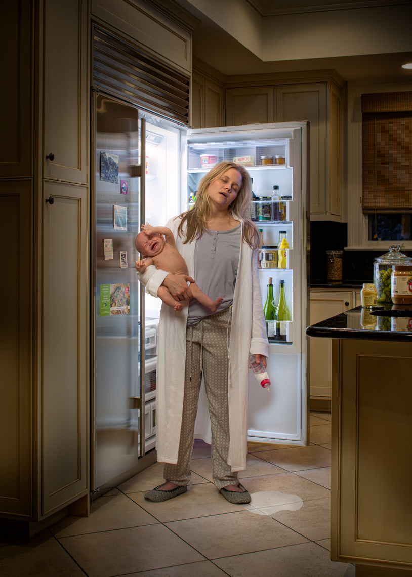 Mom feeding child at refrigerator while asleep