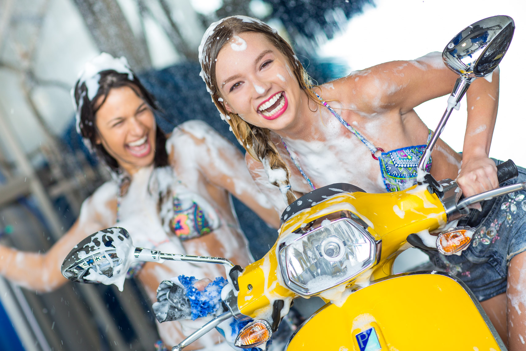 Young women driving vespa through car wash, shot by Steven P. Widoff