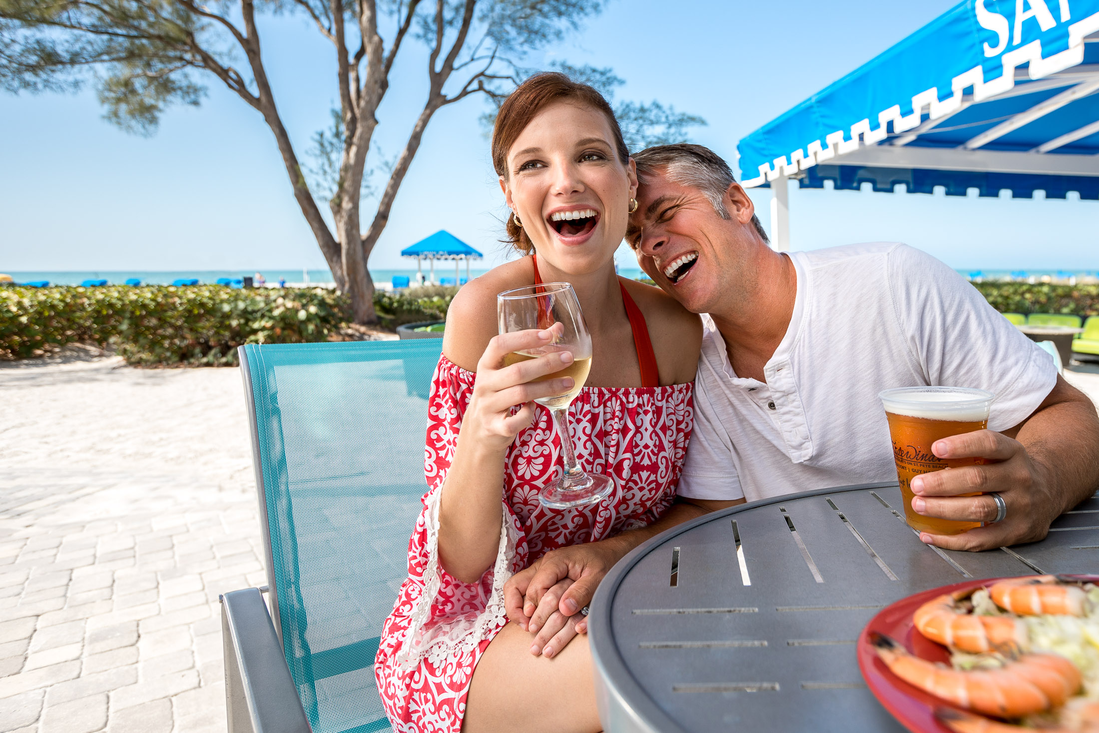 Middle aged couple laughing  at beach bar.  Photographed by Steve Widoff,