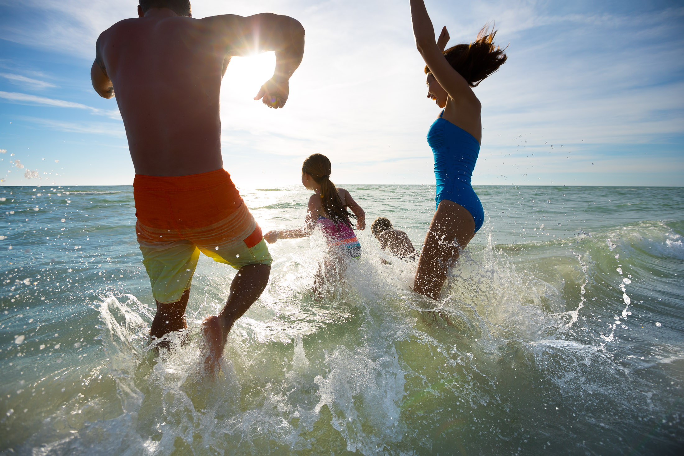 family jumping in water at beach
