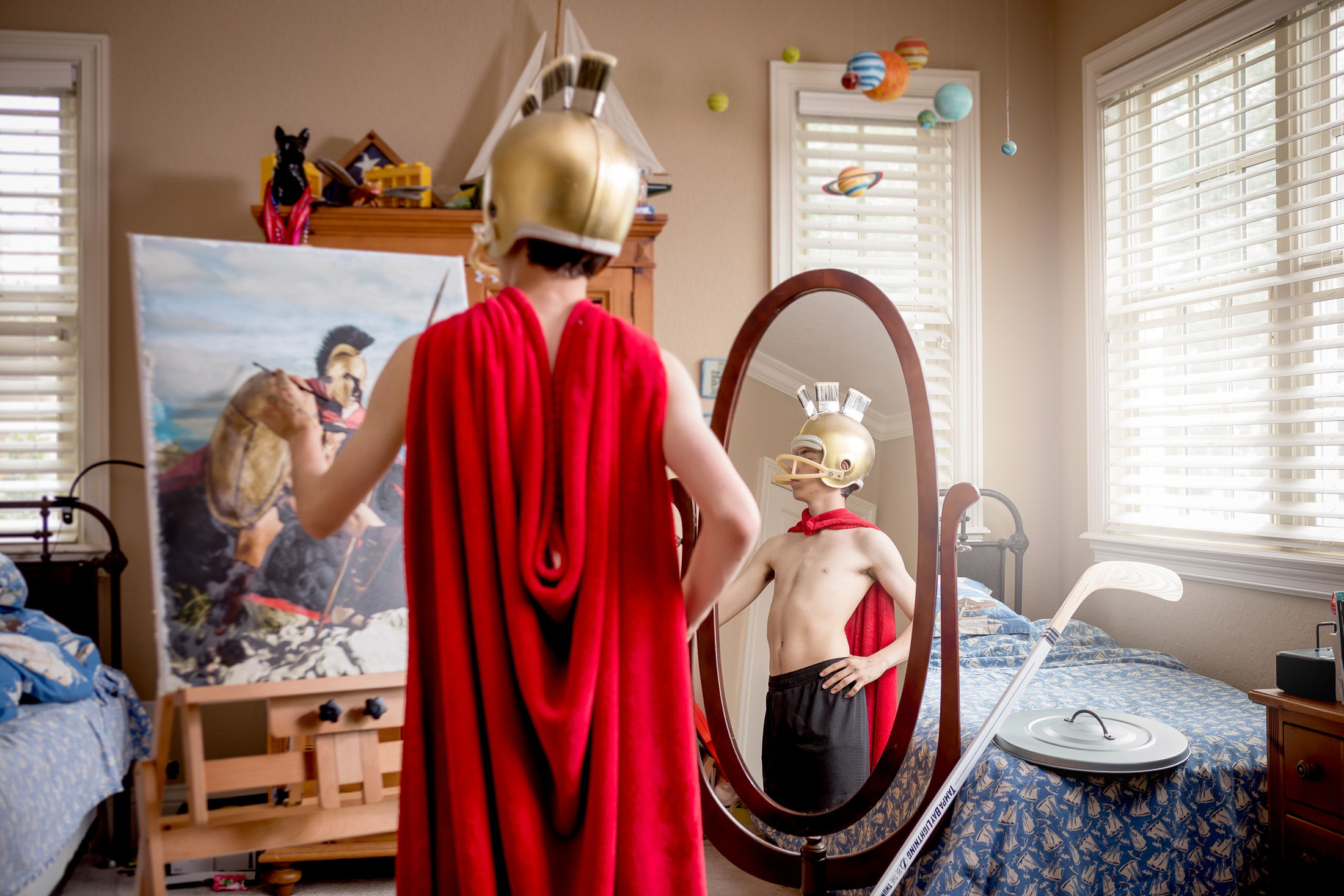 teenager dressed in gladiator costume painting a self portrait