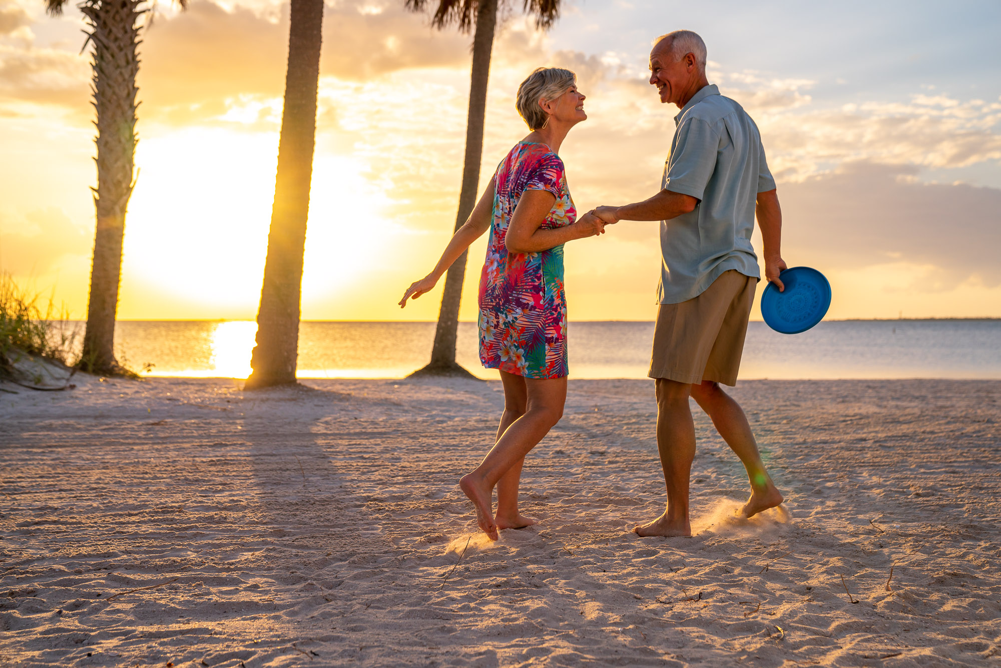senior couple on beach at sunset